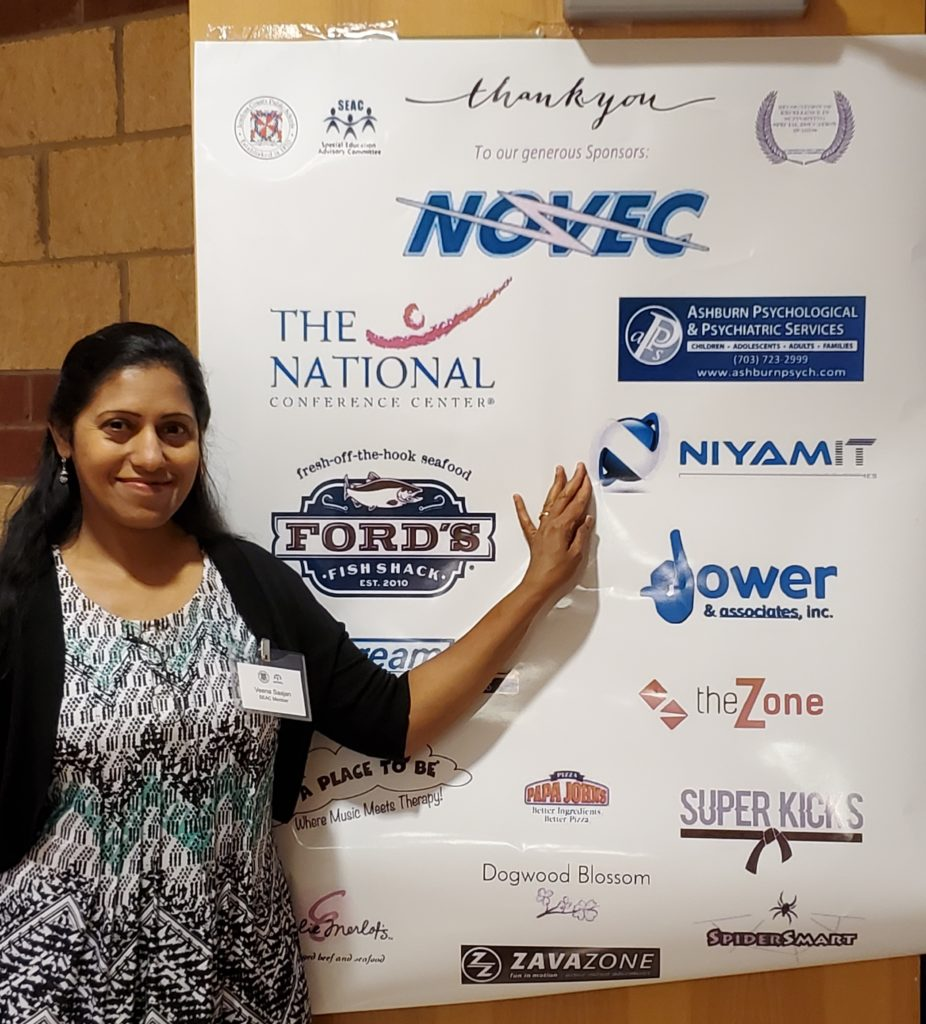 Veena standing in front of a sponsorship recognition banner with the Niyam IT logo